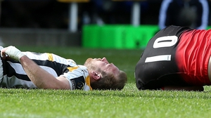 Dan Robson (l) of Wasps lies injured after a tackle by Owen Farrell (r)
