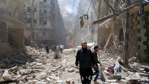 Syrians at the site of airstrikes in the rebel-held neighbourhood of Bustan Al Qasr in Aleppo