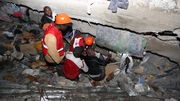 Rescuer workers search for survivors among the ruins of the building