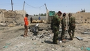Iraqi security forces stand at the site of the car bomb attack