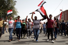 Supporters of Muqtada Al-Sadr carry the Iraqi national flag and chant slogans in front of the Green Zone in Baghdad
