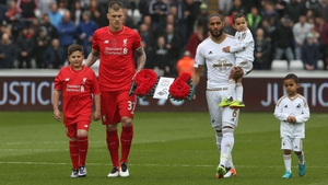 Liverpool captain Martin Skrtel and Swansea captain Ashley Williams (R) carry a wreath in memory of the 96 victims of the 1989 Hillsborough Distaster