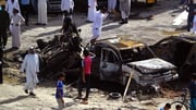 Iraqis look at the damage following a twin suicide bombing attack in the southern Iraqi city of Samawah