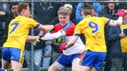 New York's Luke Loughlin runs with the ball while being pursued by Roscommon's Niall McInerney and Cathal Compton