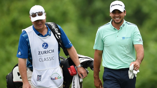 Jason Day (R) walks down the second fairway with his caddie