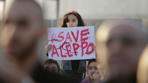 A Syrian girl holds a placard at a