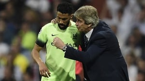 Manuel Pellegrini (R) gives instructions Gael Clichy at the Bernabeu