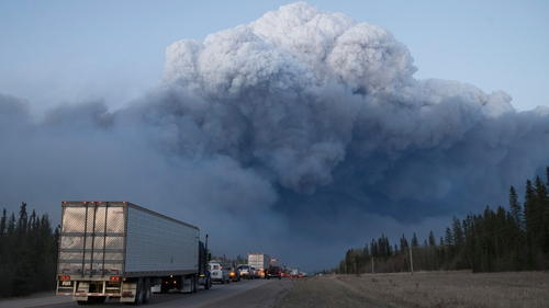 Drivers wait for clearance to take firefighting supplies into town on outside of Fort McMurray