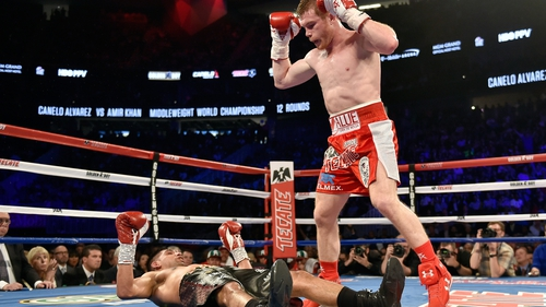 Canelo Alvarez stands over Amir Khan after delivering a knockout punch during the sixth round of their WBC middleweight title fight