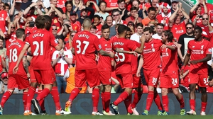 Joe Allen of Liverpool (2R) celebrates with his team-mates after he put the hosts in front