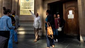 Former mine worker Vuyani Twadube (centre) celebrates as he leaves Johannesburg High Court after the judgement