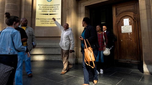Former mine worker Vuyani Twadube (centre) celebrates as he leaves Johannesburg High Court after the judgement
