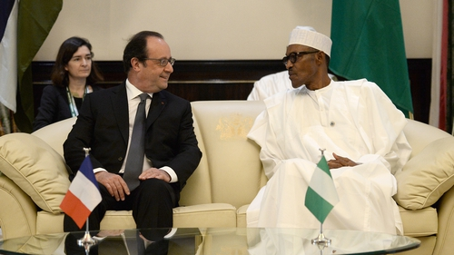 French President Francois Hollande speaks with Nigerian President Muhammadu Buhari  during a meeting at the presidential Palace in Abuja, Nigeria