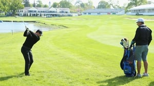 Rory McIlroy plays his second shot on the 18th hole as his caddie JP Fitzgerald looks on during practice