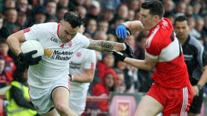 Tyrone's Cathal McCarron holds off Derry's Gareth McKinless