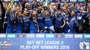 AFC Wimbledon's Barry Fuller  celebrates promotion with his team-mates