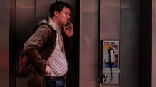 A man uses a mobile phone while standing at a pay phone in New York