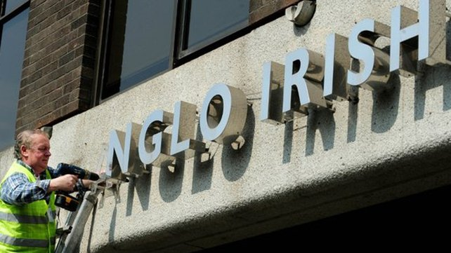 The writings off the wall - workers remove signage from outside Anglo Irish Bank in Dublin