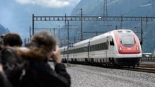 Guests who attended the opening ceremony of the tunnel take a picture of the first train crossing it