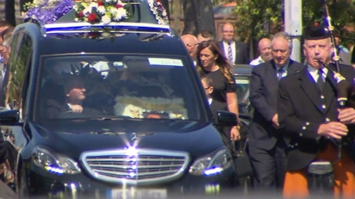 The funeral procession was ledby a lone bagpiper and the coffin was accompanied by a large crowd of mourners