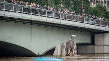 People watch the water levels of the Seine from Pont de l'Alma bridge with the partially submerged statue 'Le Zouave'