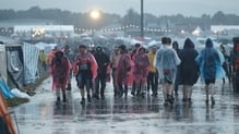 People walk through the rain at the festival yesterday