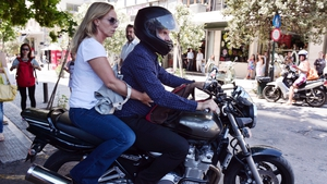 Yanis Varoufakis leaves on his motorcycle with his wife, after his resignation at the Greek ministry of Finance