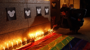 A member of an LGBT group lights candels during a vigil in honor to the victims of a mass shooting in Santiago de Chile, Chile