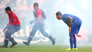 Croatian players and stewards remove flares from the field