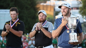 Dustin Johnson (R) poses with the US Open trophy after winning the US Open as Shane Lowry (C) and Amateur Jon Rahm (L) look on