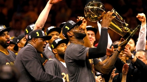 LeBron James #23 of the Cleveland Cavaliers holds the Larry O'Brien Championship Trophy