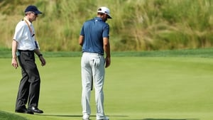 Dustin Johnson chats with a rules official on the fifth green during the final round of the U.S. Open