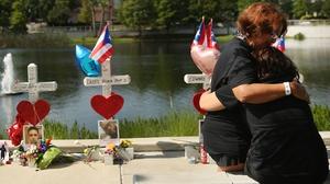 Two women embrace beside a memorial near the Pulse nightclub in Orlando, Florida