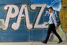 A man passes by a graffiti reading 'Peace for the people' in Cali, Colombia