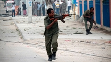 Somali security offciers take positions as they fight attackers in front of the hotel in Mogadishu, Somalia