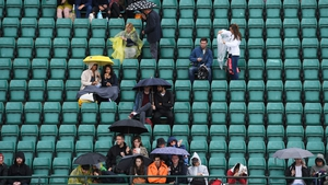 Spectators at Wimbledon take cover from the rain