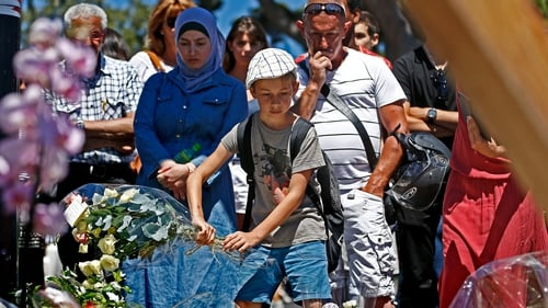People gather in front of a makeshift memorial on the 'Promenade des Anglais' in Nice