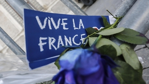 A floral tribute and message reading 'Vive la France' is left at a fence erected outside the French Embassy in Rome