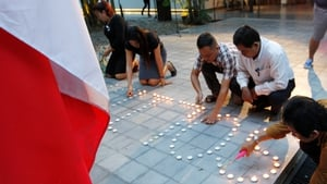 Cambodians light candles during a ceremony at French Institute in Phnom Penh