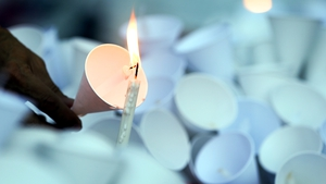 A man lights a candle during a candlelight vigil at the Alliance Francaise in Bangkok