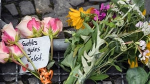 Flowers and a note that reads 'Gottes gutes Geleit' (God's safe passage) were placed in front of the French embassy in Berlin
