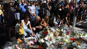 People lay flowers for the victims of the attack on the Promenade des Anglais
