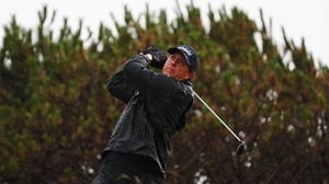 Mickelson hits a shot in full rain gear in terrible conditions at Troon on Friday