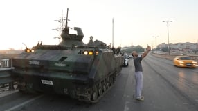 A man takes a 'selfie' against a military tank being guarded by Turkish police on the Bosphorus bridge