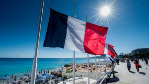 A flag is seen flying at half-mast along the 'Promenade des Anglais' where the truck crashed into the crowds on Thursday