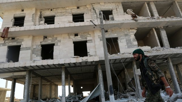 A member of the US-backed Kurdish and Arab fighters walks past destroyed buildings as they advanced into Manbij in June
