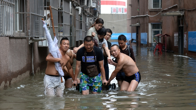 Locals make their way through a flooded area in Changping District in Beijing
