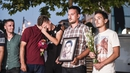 People mourn in Pristina, Kosovo, as they hold flowers and a picture of Diamant Zabergja, one of the victims that was shot dead in the Munich attack