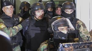 Jose Lopez (C) is taken into custody after his arrest last month