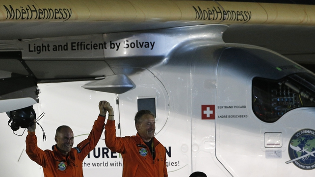 Bertrand Piccard (L) and André Borschberg are greeted upon Piccard's arrival in Abu Dhabi